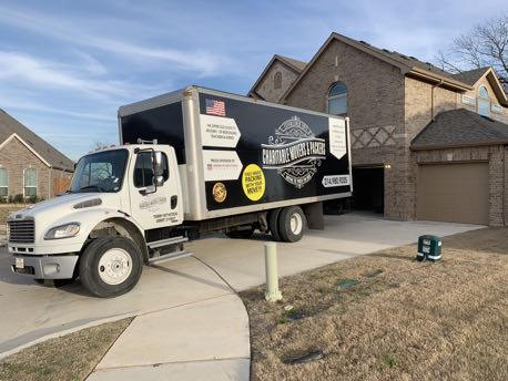 Image: Charitable Mover & Packers moving truck parked at a house.